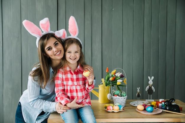Jonge vrouw die dochter in konijntjesoren koestert