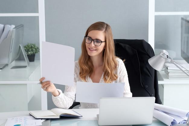 Jonge vrouw die documenten bekijkt