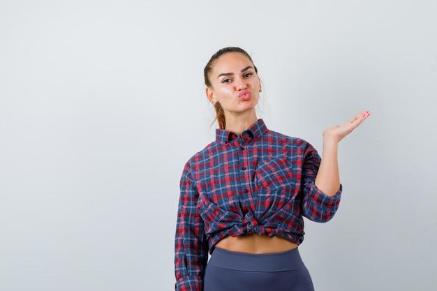 Jonge vrouw die doet alsof ze iets laat zien terwijl ze lippen pruilt in geruit hemd, broek en er schattig uitziet, vooraanzicht.