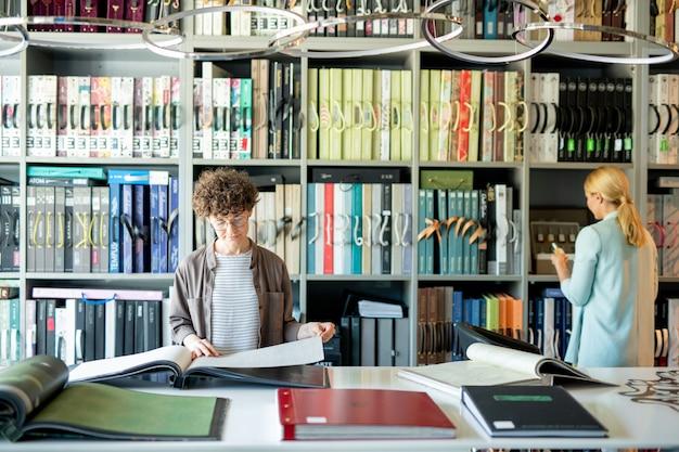 Jonge vrouw die door catalogus van binnenlands ontwerp kijkt terwijl een andere cliënt zich door planken bevindt
