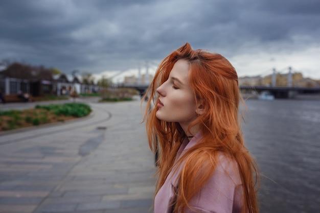 Jonge vrouw die door de straten van moskou loopt. wandelen op boulevard. gorky park in het vroege voorjaar of de herfst