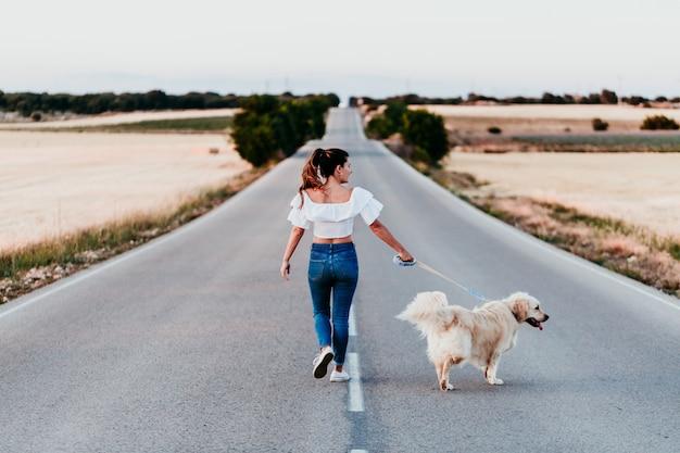 Jonge vrouw die door de weg met haar golden retrieverhond bij zonsondergang loopt. huisdieren buiten