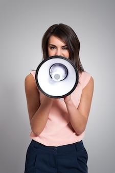 Jonge vrouw die door megafoon gilt