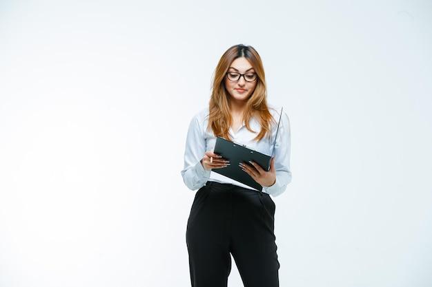 Jonge vrouw die door open klembord kijkt