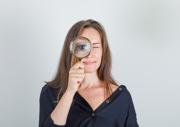 Jonge vrouw die door vergrootglas in zwart overhemd kijkt