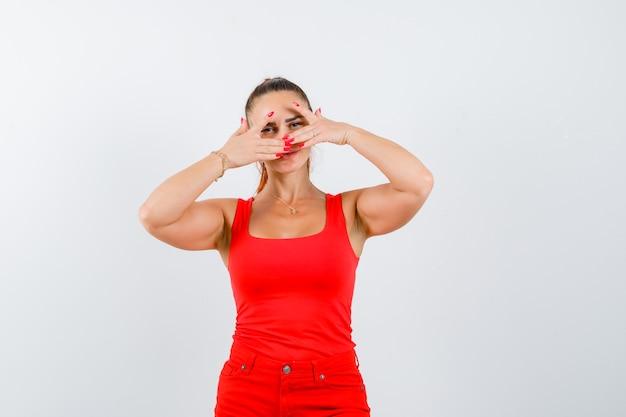 Jonge vrouw die door vingers in rood mouwloos onderhemd, broek kijkt en wantrouwend, vooraanzicht kijkt.