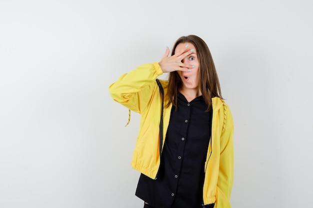 Jonge vrouw die door vingers kijkt en verbaasd kijkt