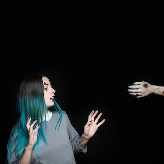 Jonge vrouw die door zombiewapen wordt verbaasd