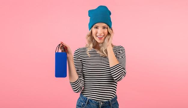 Jonge vrouw die draadloze spreker houdt die aan muziek luistert die een gestreept overhemd en een blauwe hoed draagt die die zich op roze stelt glimlachend