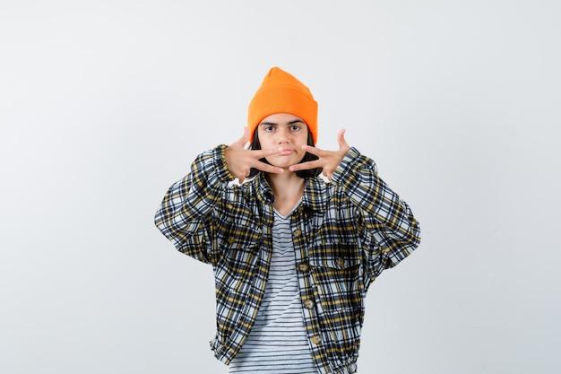 Jonge vrouw die drie vingers in oranje hoed en geruit overhemd toont en ongelukkig kijkt