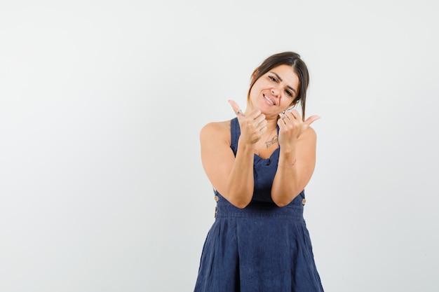 Jonge vrouw die dubbele duimen in kleding toont en vreugdevol kijkt
