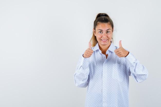 Jonge vrouw die dubbele duimen in wit overhemd toont en gelukkig kijkt