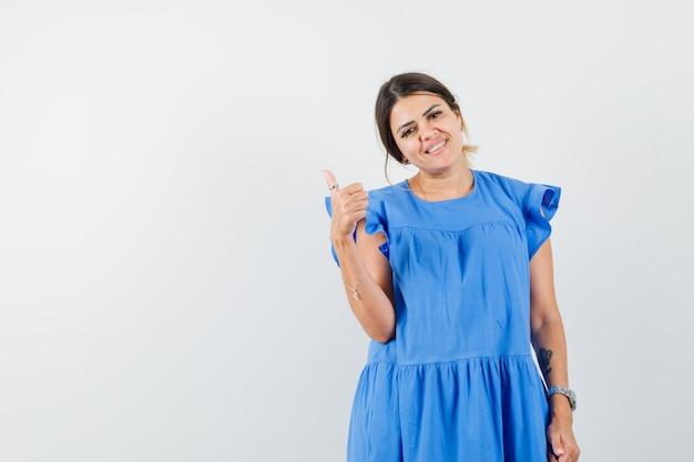Jonge vrouw die duim in blauwe kleding toont en vrolijk kijkt