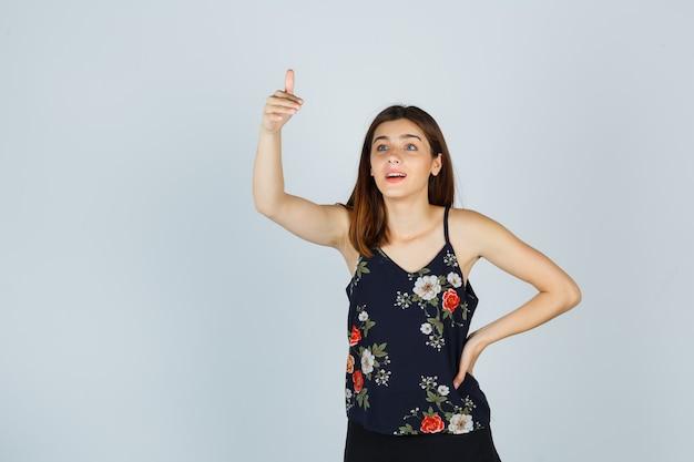 Jonge vrouw die duim in blouse toont en zich afvroeg, vooraanzicht.