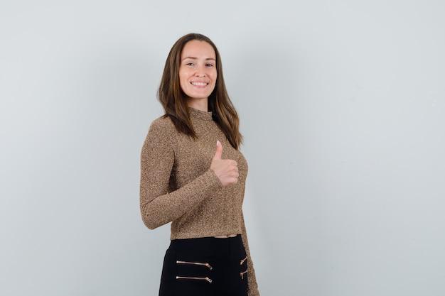 Jonge vrouw die duim in goud vergulde sweater en zwarte broek toont en gelukkig kijkt