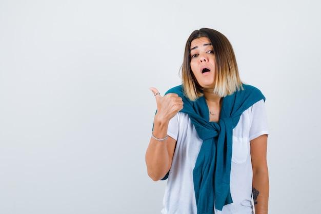 Jonge vrouw die duim in wit t-shirt toont en verrast kijkt, vooraanzicht.