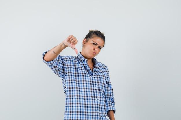 Jonge vrouw die duim neer in geruit overhemd toont en boos kijkt.