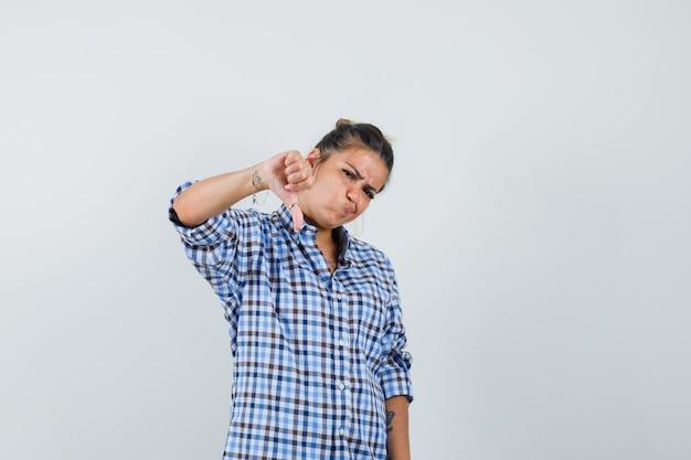 Jonge vrouw die duim neer in geruit overhemd toont en ontevreden kijkt.