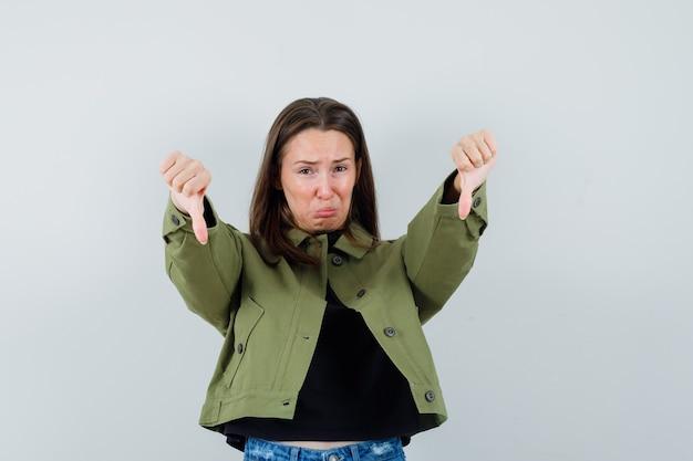 Jonge vrouw die duim neer in groen jasje toont en boos, vooraanzicht kijkt.