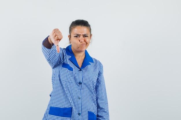 Jonge vrouw die duim neer in het blauwe overhemd van de gingangpyjama toont en ontevreden kijkt. vooraanzicht.