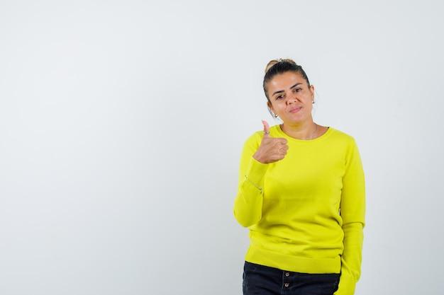 Jonge vrouw die duim opduikt in gele trui en zwarte broek en er gelukkig uitziet