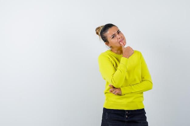 Jonge vrouw die duim toont en hand op elleboog houdt in gele trui en zwarte broek en er tevreden uitziet