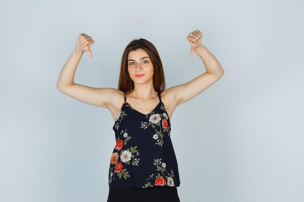 Jonge vrouw die duimen neer in bloemenbovenkant toont en weemoedig kijkt