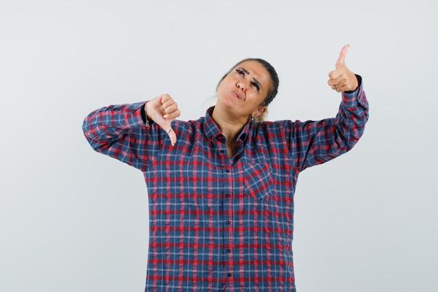Jonge vrouw die duimen op en neer in gecontroleerd overhemd toont en onbeslist kijkt. vooraanzicht.