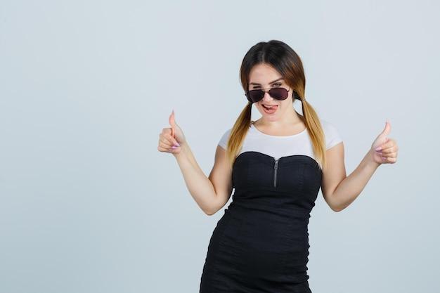 Jonge vrouw die duimen opsteekt terwijl ze knipoogt