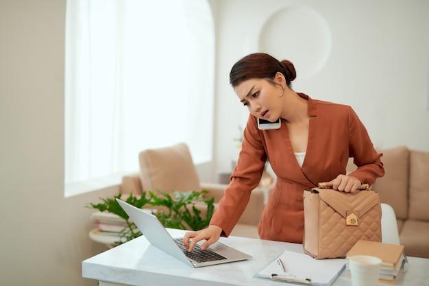 Jonge vrouw die e-mails controleert op kantoor