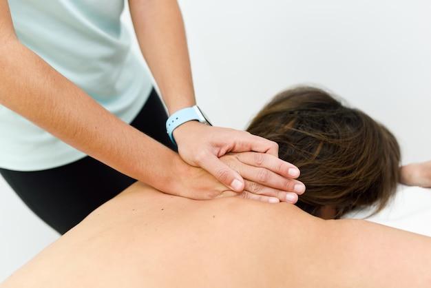 Jonge vrouw die een achtermassage in een kuuroordcentrum ontvangt.