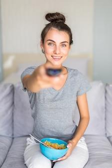 Jonge vrouw die een afstandsbediening houdt die thuis op de laag zit en op tv met salade let