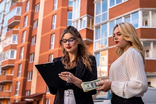 Jonge vrouw die een appartement in een nieuw huis heeft gekocht, tekent een deal met een makelaar. verkoop of huur concept