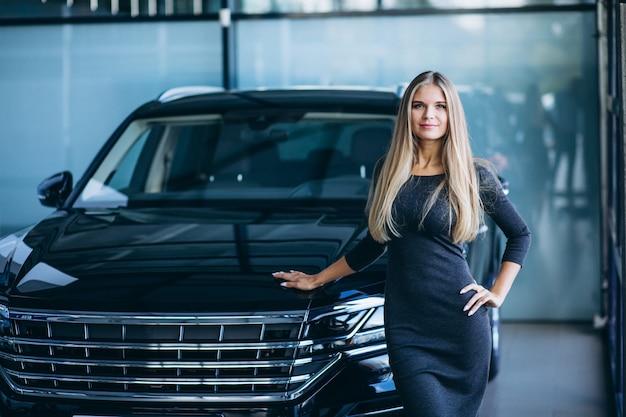 Jonge vrouw die een auto in een autotoonzaal kiest