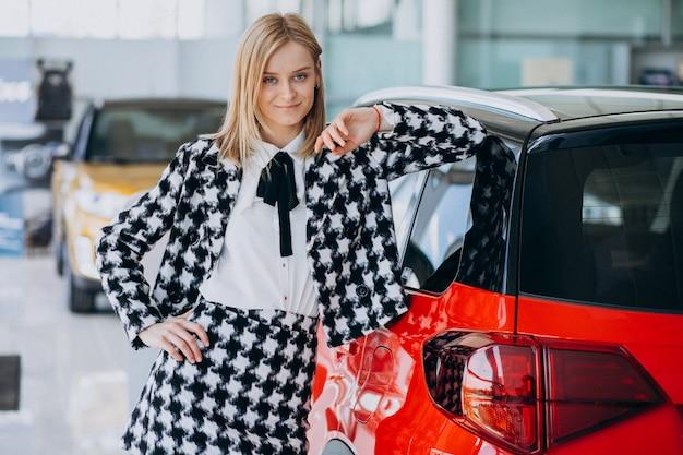Jonge vrouw die een auto in een autotoonzaal koopt