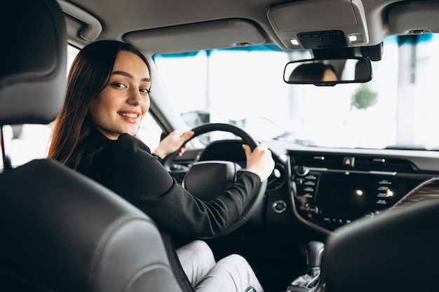 Jonge vrouw die een auto in een autotoonzaal test