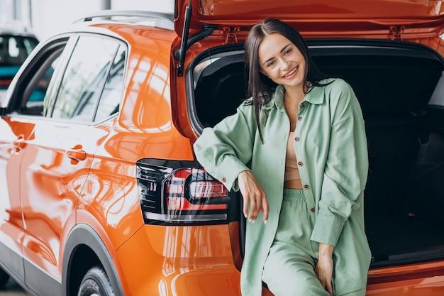 Jonge vrouw die een auto voor zichzelf kiest
