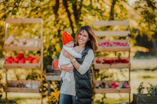 Jonge vrouw die een babymeisje in rode pompoenhoed houden op de openluchtplaats van de landbouwbedrijfmarkt.