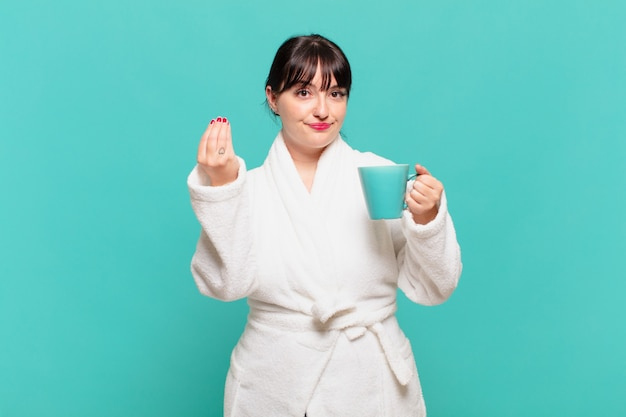 Jonge vrouw die een badjas draagt die capice of geldgebaar maakt, die u vertelt om uw schulden te betalen!