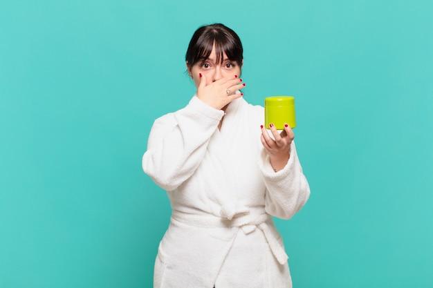 Jonge vrouw die een badjas draagt die de mond bedekt met handen met een geschokte, verbaasde uitdrukking, een geheim bewaart of oeps zegt