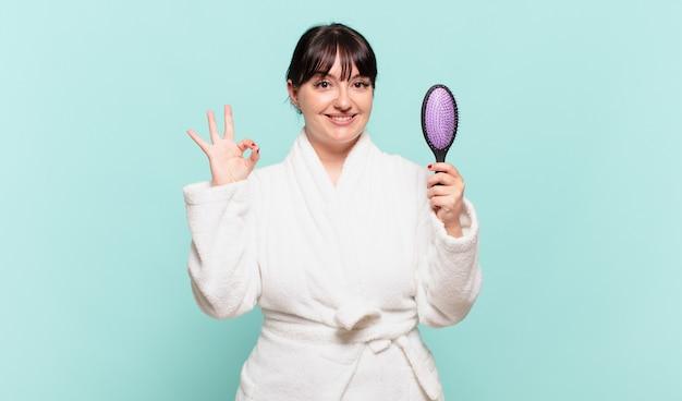 Jonge vrouw die een badjas draagt die zich gelukkig, ontspannen en tevreden voelt, goedkeuring toont met een goed gebaar, glimlachend