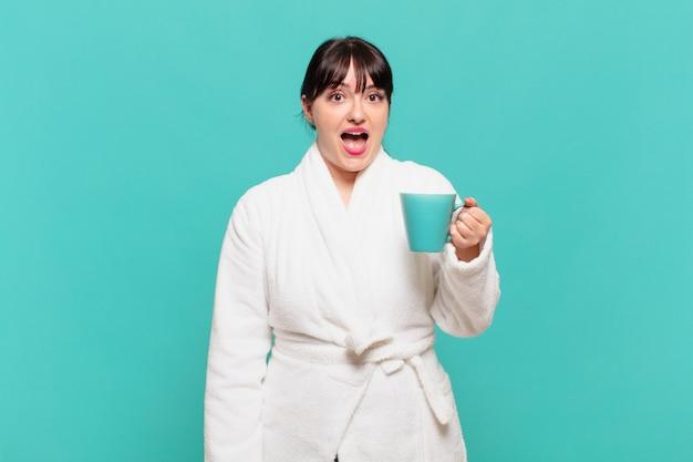 Jonge vrouw die een badjas draagt en er blij en aangenaam verrast uitziet, opgewonden met een gefascineerde en geschokte uitdrukking