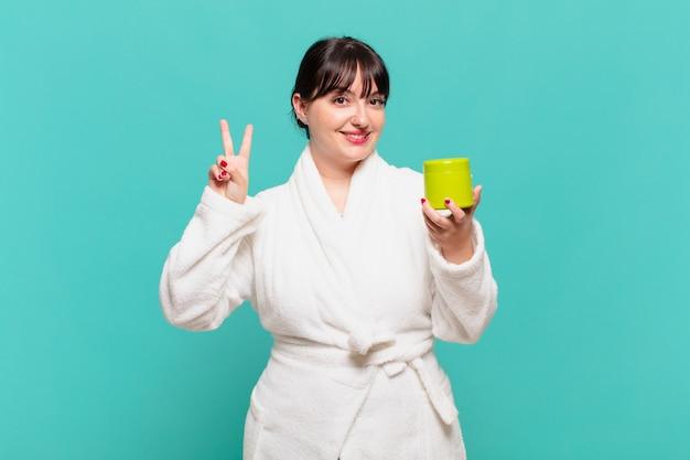 Jonge vrouw die een badjas draagt en er vriendelijk uitziet, met nummer twee of seconde met de hand naar voren, aftellend