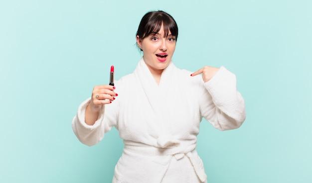 Jonge vrouw die een badjas draagt, voelt zich gelukkig, verrast en trots, wijzend naar zichzelf met een opgewonden, verbaasde blik