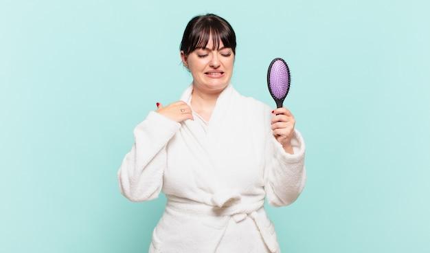 Jonge vrouw die een badjas draagt, voelt zich gestrest, angstig, moe en gefrustreerd, trekt aan de nek van het shirt, ziet er gefrustreerd uit met een probleem