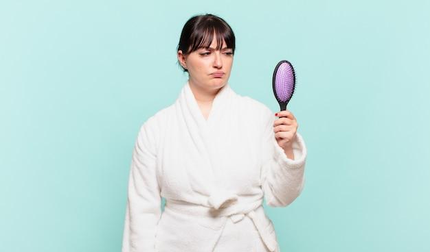 Jonge vrouw die een badjas draagt, voelt zich verdrietig, overstuur of boos en kijkt opzij met een negatieve houding, fronsend in onenigheid