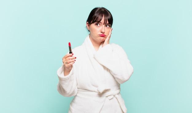 Jonge vrouw die een badjas draagt, voelt zich verveeld, gefrustreerd en slaperig na een vermoeiende, saaie en vervelende taak, gezicht met de hand vasthoudend