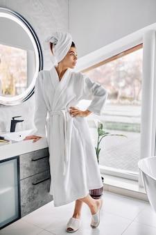 Jonge vrouw die een badjas en een handdoek op haar haar draagt
