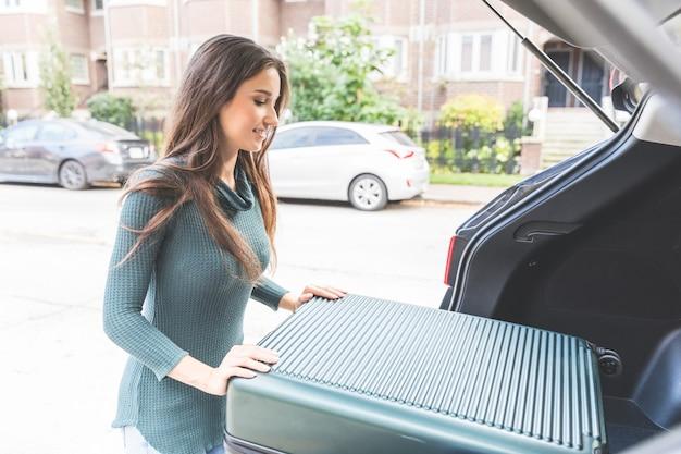 Jonge vrouw die een bagage in de auto laadt