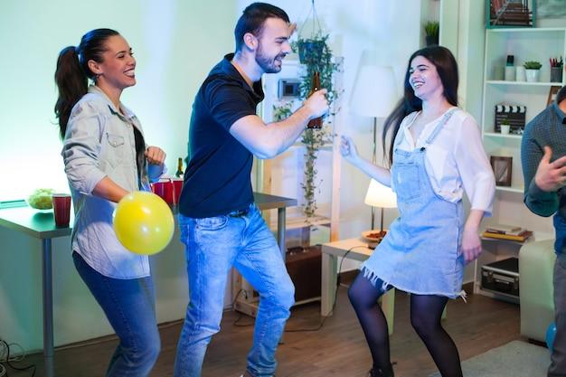 Jonge vrouw die een ballon vasthoudt terwijl ze danst met haar vrienden op een feestje. man met een bierfles.